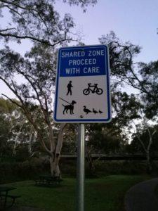 anuncio con bicicleta, peatón, perro y patos